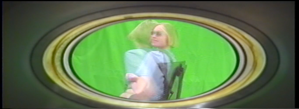 Two exposures of a person spinning around in front of a unedited green screen. The lens's barrel frames the shot.