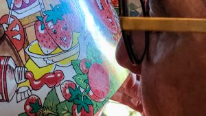 A person leaning into a book to smell a scratch and sniff sticker applied to the page.